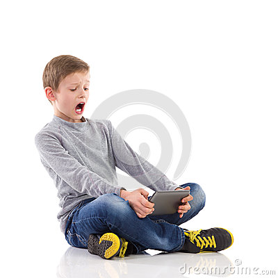 Shouting boy using a tablet.
