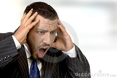 Shouting businessman holding his head in his hands