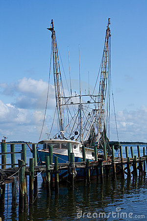 Shrimp boat docked by pier