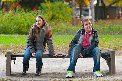 Shy boy and the girl sitting in the park Stock Photo