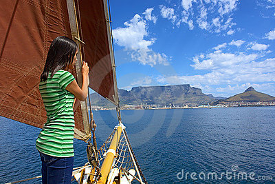 Shy girl on yacht with red sails looks at waves