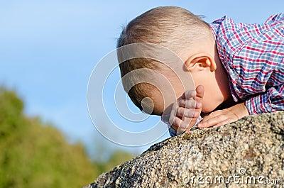 Shy little boy hiding has face