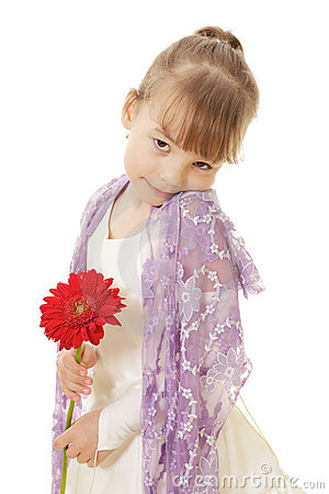 Shy little girl in dress holding red flower