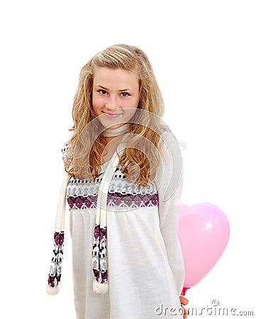 Shy teenage girl hiding a heart ballon behind