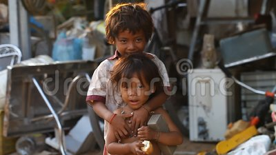 Siam Reap, Cambodia - January 14, 2017: A homeless boy with his young sister living in a house from empty boxes and. Construction debris. Homeless and orphaned stock video footage