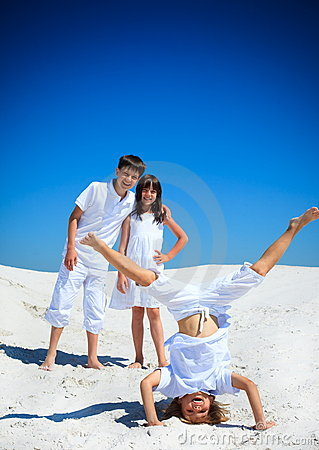 Sibling playing on white beach