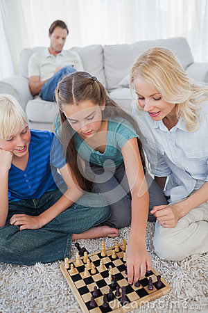 Free Siblings And Mother Playing Chess Sitting On A Carpet Stock Image - 31670191