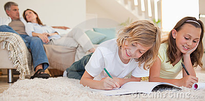 Siblings doing their homework on the carpet
