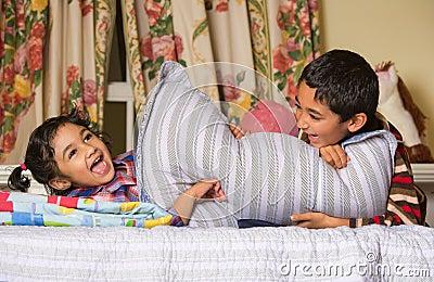 Siblings Enjoying a Pillow Fight