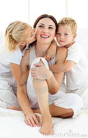 Siblings hugging their mother sitting on a bed
