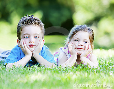 Siblings laying in the grass