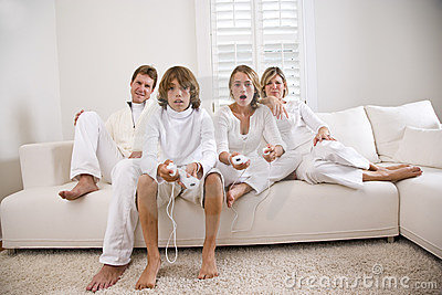 Siblings playing video game while parents watch