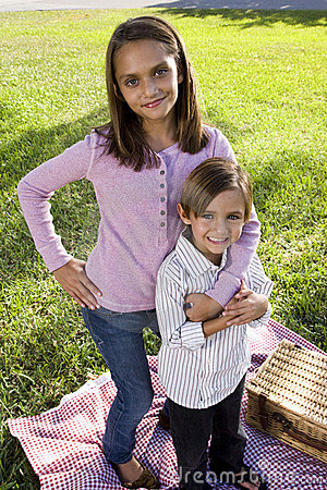 Siblings posing for camera having picnic in park