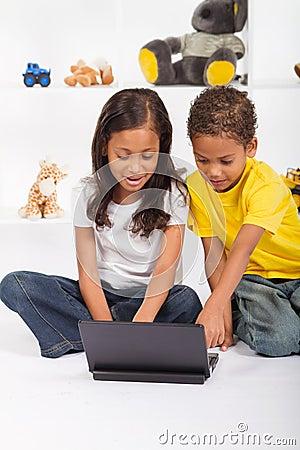 Siblings using laptop