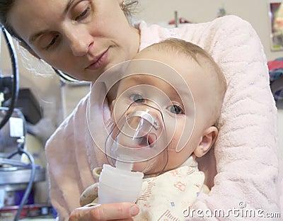 Sick baby with nebulizer mask