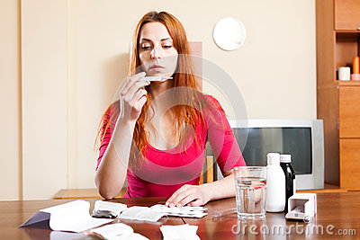Sick beautiful young woman looks at thermometer at home
