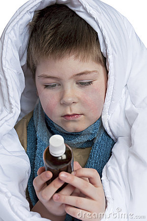Sick boy in a blanket looking at a bottle