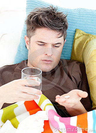 Sick caucasian man taking pills with water