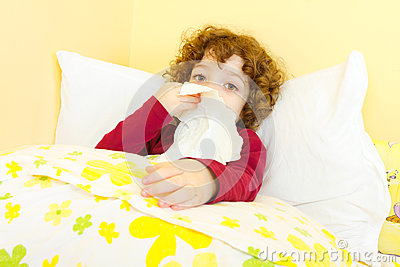 Sick child in bed blowing her nose