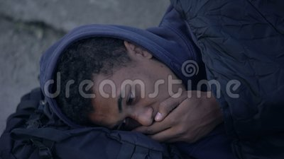 Sick coughing homeless man sleeping outdoors, social insecurity, poverty despair. Stock footage stock video