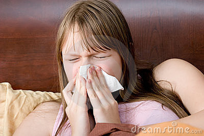 Sick with flu teenager girl in bed sneezing