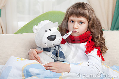 Sick girl with thermometer embraces toy in bed