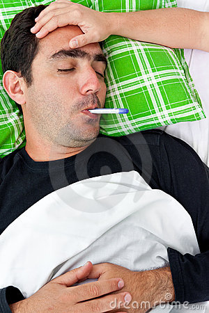 Sick hispanic man laying in bed with a thermometer
