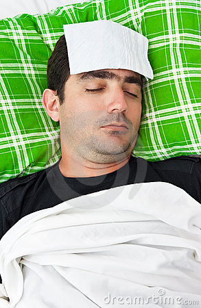 Sick man in bed with a tissue in his forehead