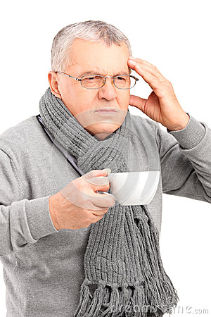 Sick mature man holding a cup of tea and gesturing headache