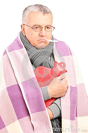 Sick senior with thermometer in his mouth, covered with blanket