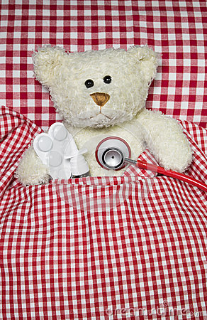Sick teddy bear lying in a red checked bed. Concept for illness.