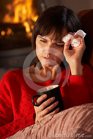 Sick Woman With Cold Resting On Sofa