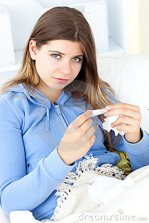 Sick woman holding tissues sitting on a sofa