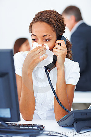 Sick young business woman blowing her nose