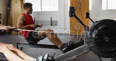 Sida vid sida av idrottsliga kaukasiska vänner som tränar på en roddmaskin stock video