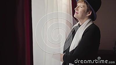 Sida vid sida av självsäker kaukasisk högre kvinna som tittar ut genom fönstret, fixerar elegant hatt och lämnar Stående av arkivfilmer