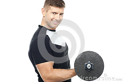 Side pose of gym instructor lifting weights