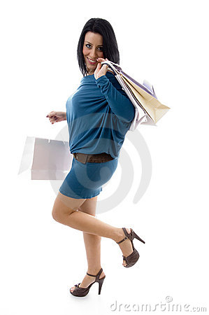 Side pose of smiling model holding carry bags