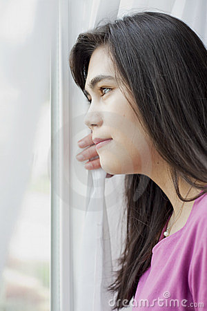 Side profile of teen girl looking out window