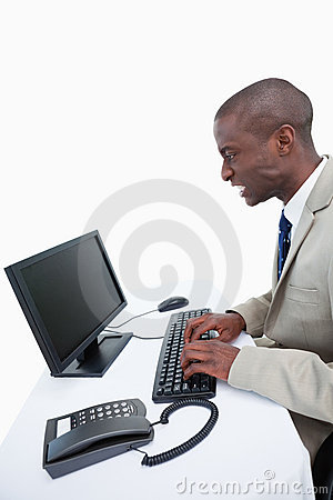 Side view of an angry businessman using a computer