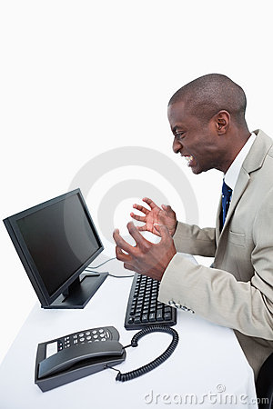 Side view of an angry businessman using a monitor