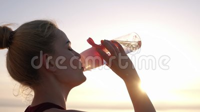 Side view of beautiful girl in sport clothes opens her pink coloured sport bottle and drinking water after workout near. The sea. Morning stock footage