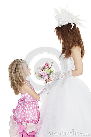 Side view of bride and bridesmaid looking at each other while holding bouquet over white background
