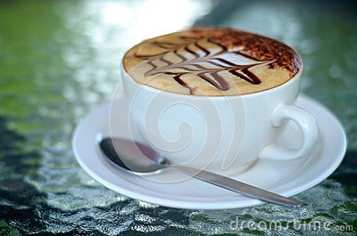 Side view of cappuccino coffee cup with spoon