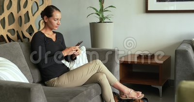 Side view of Caucasian woman using mobile phone on sofa in lobby at hospital 4k. Side view of Caucasian woman using mobile phone on sofa in lobby at hospital stock footage