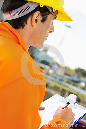 Side view of construction worker writing on clipboard at construction site