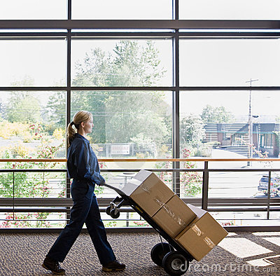 Side view of delivery woman pushing stack of boxes