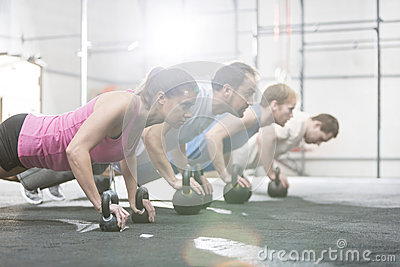 Side view of determined people doing pushups with kettlebells at crossfit gym Stock Photo