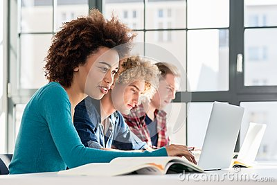 Student smiling while using a laptop for online information or v Stock Photo