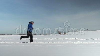 The side view of the man running in winter stock footage